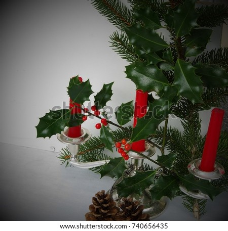 France, Rhone/Alps, Ferney Voltaire, October 2017: Christmas decorations - an element of the Christmas tree, Silver candle holder with 3 red candles, branch with leaves of  Holly and two cones.