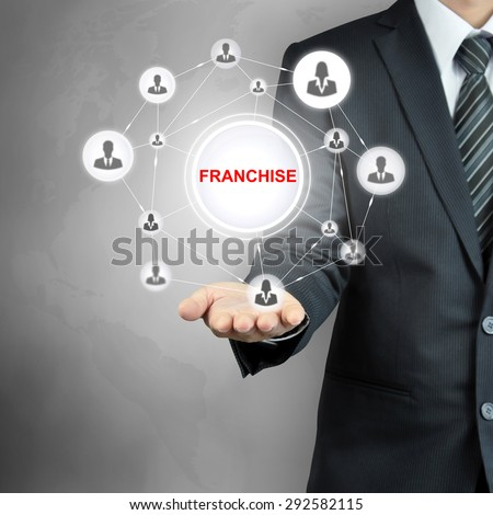 FRANCHISE sign with people icon network on businessman hand - stock photo