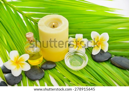 frangipani and candle ,oil ,black stones on palm leaf - stock photo