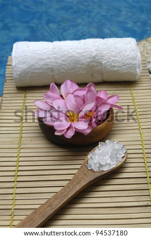 frangipani and herbal salt in spoon and towel on mat in the swimming pool - stock photo