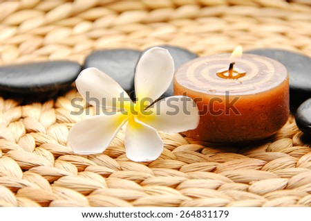 frangipani and stones ,candle on Wicker placemat - stock photo