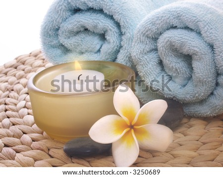 frangipani,candle and blue towel on mat - stock photo