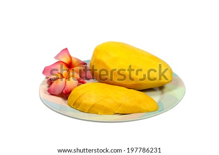 Frangipani flower and Ripe mango on dish. - stock photo