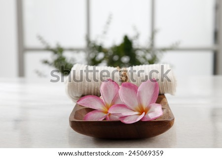 frangipani flower,salt and towel in a wooden bowl - stock photo