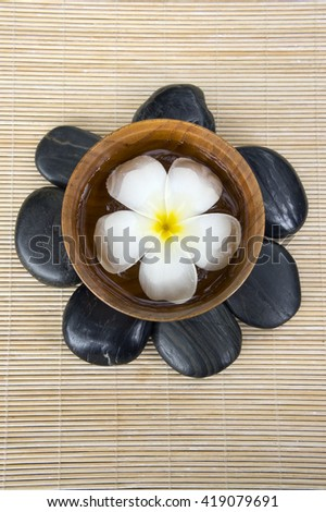 Frangipani, hot and cold stone on bamboo mat - stock photo