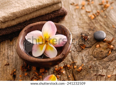 frangipani in bowl and stones ,dry flower petals ,towel on old wood  - stock photo