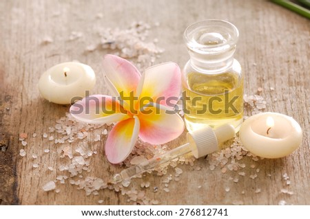 frangipani, oil and pile of salt,candle on wooden