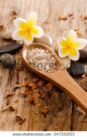 frangipani,stones with dry flower petals and salt in spoon on old wood  - stock photo