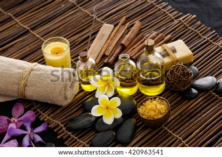 frangipani with stones ,candle, oil ,soap on mat background  frangipani with stones ,candle, oil ,soap on mat background   - stock photo