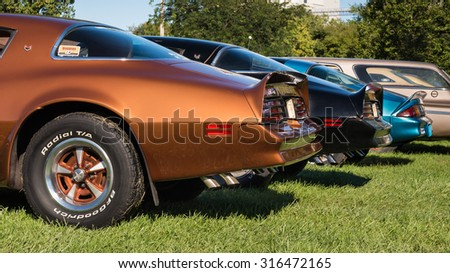FRANKENMUTH, MI/USA - SEPTEMBER 13, 2015: Two Pontiac Firebird Trans Am cars and a Chevrolet Camaro Z/28 at the Frankenmuth Auto Fest, held in Heritage Park. - stock photo