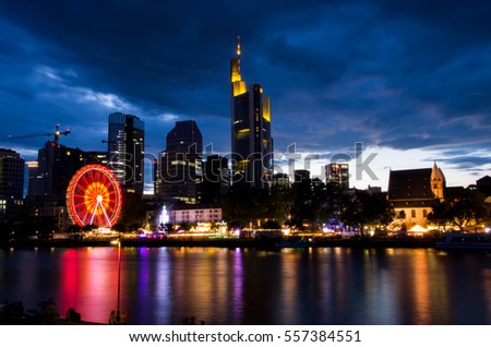 Frankfurt am Main,  Germany - August 05 2016: Ferris wheel and rides on the bank of river Main in Frankfurt am Main.