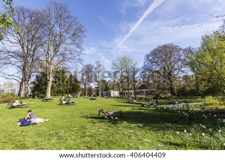 FRANKFURT, GERMANY - APR 15, 2015: people enjoy relaxing in the outdoor area of the  Palmengarten in Frankfurt. The palmengarten was founded in 1869 by citizens of Frankfurt. - stock photo
