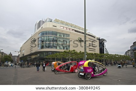 Frankfurt, Germany - April 28, 2014: Bicycle taxis and people walking in front of Galeria department store in central Frankfurt, Germany on April 28, 2014