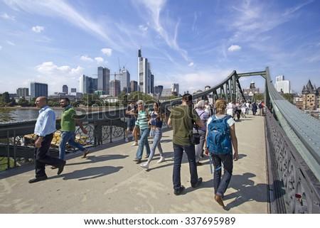 Frankfurt, Germany - August 29, 2013: People walk on the iron footbridge across the Main river in Frankfurt, Germany on August 29, 2013. - stock photo
