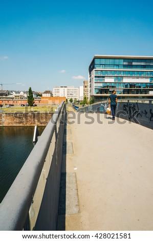 FRANKFURT, GERMANY- AUGUST 22 , 2015: People walking on the bridge at Westhafen , Frankfurt. - stock photo