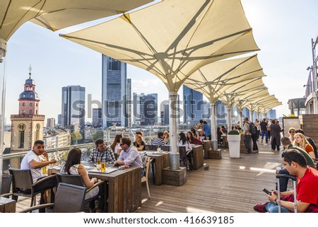 FRANKFURT, GERMANY - MAY 6, 2016: people enjoy the view from the panorama platform to the skyline in Frankfurt, Germany. The Kaufhof platform is open to public from 9.30 am to 9 pm and is free.