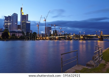 FRANKFURT, GERMANY - MAY 9. The river Main, skydcrapers of the biggest banking companies and the Untermain Bridge in Frankfurt with dark grey rain clouds in the evening of May 9, 2014.