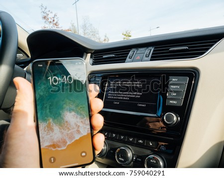 FRANKFURT, GERMANY - NOV 4, 2017: Man connecting his new iPhone X 10 to the navigation system of the car with CarPlay - message on GPS - new device detected