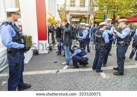FRANKFURT, GERMANY - OCT 3, 2015: Demonstrant is being checked by police during the 25th anniversary of German Unity in Frankfurt, Germany.