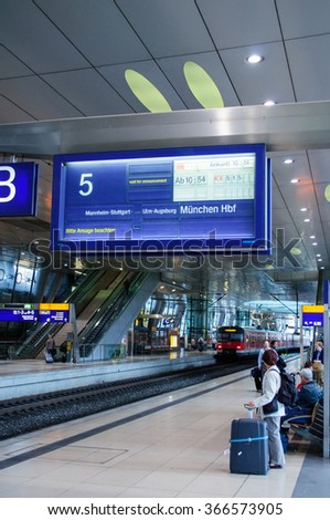 FRANKFURT, GERMANY - SEPTEMBER 14, 2009: Vintage train information boarding board at Frankfurt Airport Train station with people commuting on the platform during rush hour - stock photo