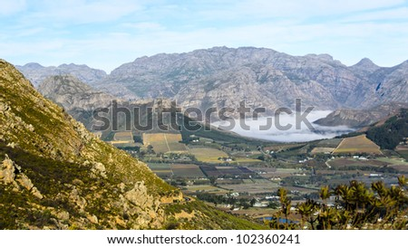 Franschhoek early morning  with a blanket of clouds over it - stock photo
