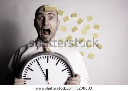 Frantic, unorganized businessman unsuccessfully tries to use many post-it notes to remind him of his busy schedule and appointments. - stock photo