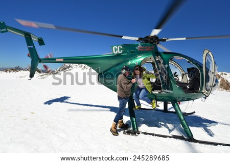 FRANZ JOSEF GLACIER, NEW ZEALAND: November 16, 2014: passengers alight from a helicopter onto the snow above Franz Josef Glacier, Westland, New Zealand - stock photo