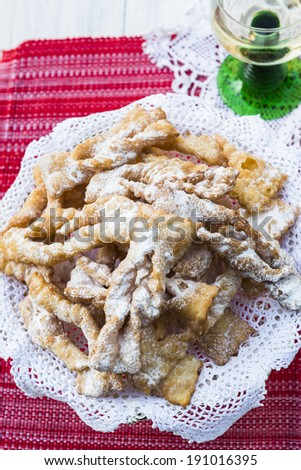 Frappe - typical Italian carnival fritters dusted with icing sugar, with a glass of desert wine in the background  - stock photo
