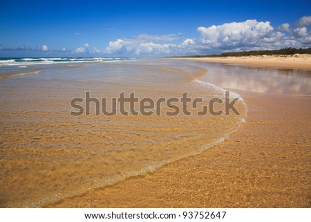 Fraser Island 70 mile beach clear sand, waver of sea water blue sky and nobody - stock photo