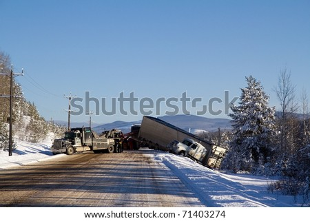 FRASER LAKE BC CANADA  FEBRUARY 15: Days of heavy snow fall and cold temperatures led to icy roads causing numerous accidents including this jack knifed transport truck Fraser Lake on February 15 2011 - stock photo