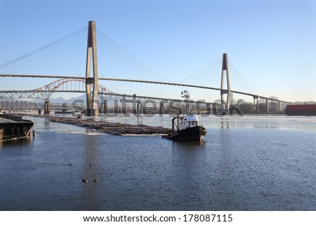 Fraser River Winter Log Boom. Tugboats maneuver a log boom under three bridges crossing the Fraser River in New Westminster, British Columbia, Canada.  - stock photo