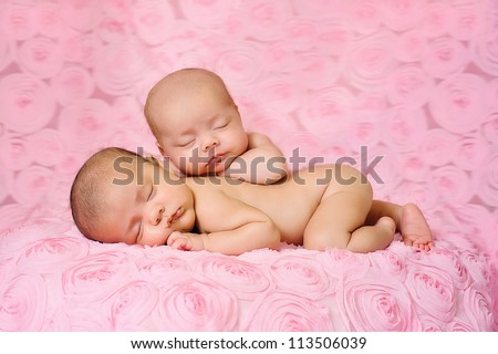 Fraternal twin newborn baby girls sleeping on pink, three dimensional rose fabric. One baby is lying on her stomach and the other is propped on top of her sister. - stock photo