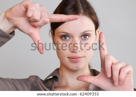Frau schut durch die Finger. - stock photo