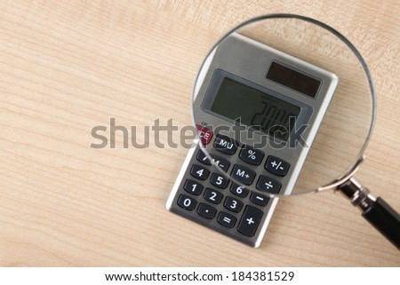 Fraud concept with magnifier and calculator, on wooden background - stock photo