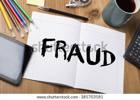 FRAUD - Note Pad With Text On Wooden Table - with office  tools - stock photo