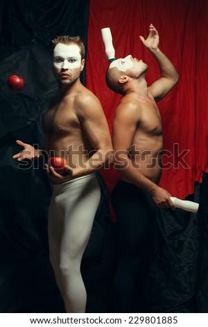 Freak circus concept. Two muscular mime artists, clowns with white masks on faces juggling and posing over red cloth & black background. Vintage style. Studio shot - stock photo