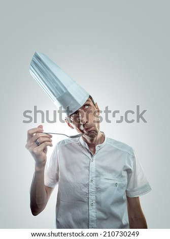freaky chef with a kitchen spoon. tasting a dish. - stock photo