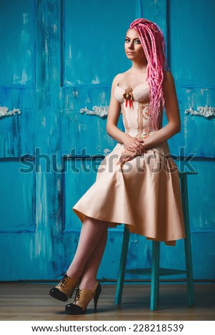 Freaky young woman in vintage corset with rose flower decoration sitting against rusty blue turquoise background. Bright pink dreadlocks hairstyle, beauty make up.