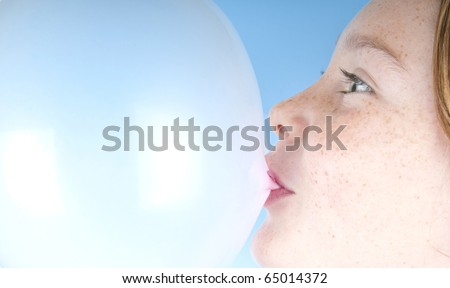 freckle faced girl blowing bubble with gum - stock photo