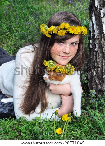 freckled girl and cat in flowers wreaths in the spring park - stock photo