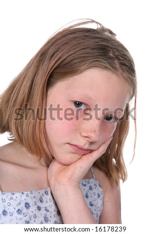 freckled girl with chin on hand and looking sad