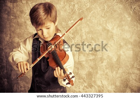 Freckled nine year old boy playing the violin. Musical education. Inspiration. - stock photo