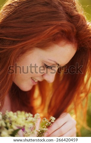 Freckled red-haired girl with a bouquet of flowers