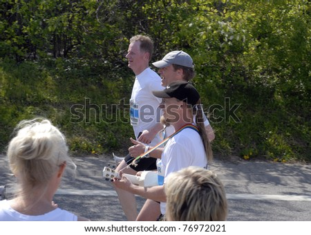 FREDERICIA, DENMARK - MAY 7: Three men from Sweden called Band On The Run playing and running on Kystvejen in Fredericia at The Little Belt Half Marathon May 7. 2011.