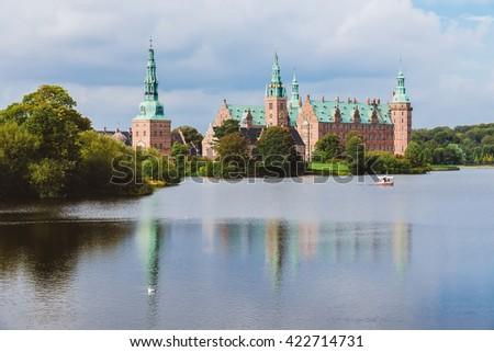 Frederiksborg castle reflected in the lake in Hillerod, Denmark. Renaissance castle, romantic lake and park near Copenhagen. - stock photo