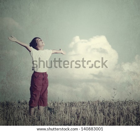 Free child dreaming with outstretched hands on beautiful meadow with clouds in background - stock photo