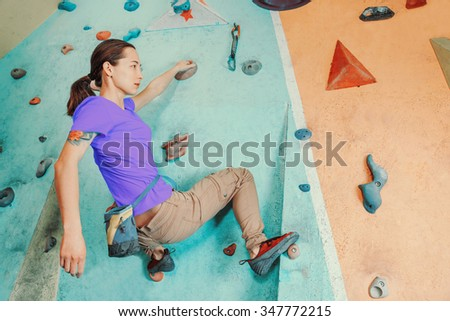 Free climber young woman training on artificial boulder wall indoors
