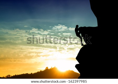Free climbing man at sunset - stock photo
