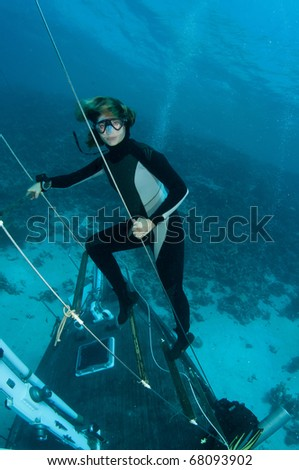 Free diver stands on underwater wreck - stock photo
