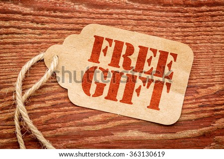 free gift sign - red stencil text a paper price tag against rustic wood - stock photo